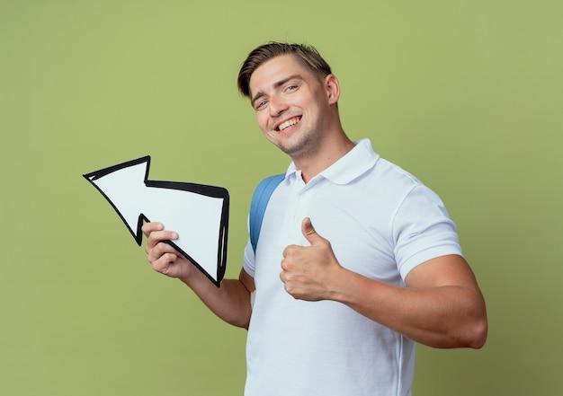Uśmiechnięty młody przystojny student płci męskiej ubrany w torbę trzymając kierunek znak kciuk w górę na białym tle na oliwkowym tle