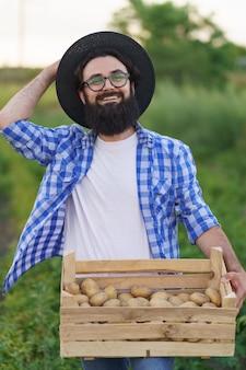 Uśmiechnięty młody rolnik trzymający drewnianą skrzynię ziemniaków na zielonym polu ziemniaków