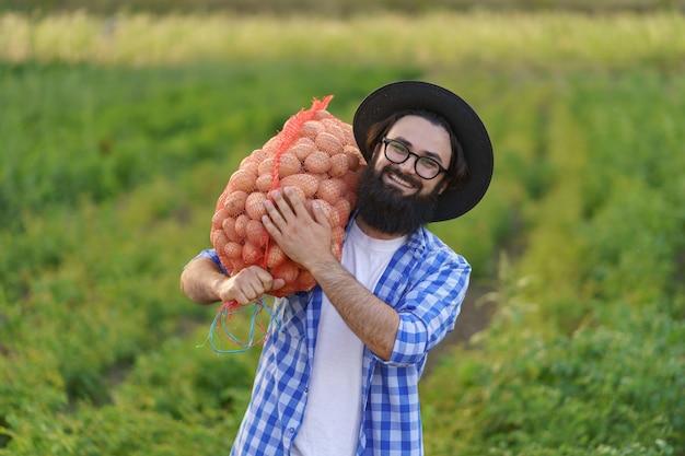 Uśmiechnięty młody rolnik trzymający worek świeżych ziemniaków na zielonym polu ziemniaków