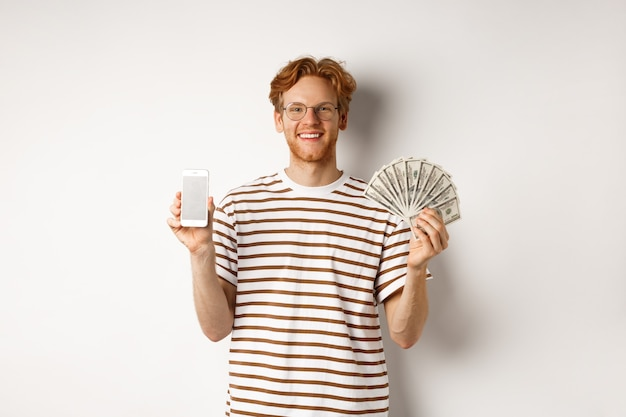Uśmiechnięty młody rudy mężczyzna w okularach pokazuje pusty ekran smartfona i pieniądze, stojąc na białym tle.