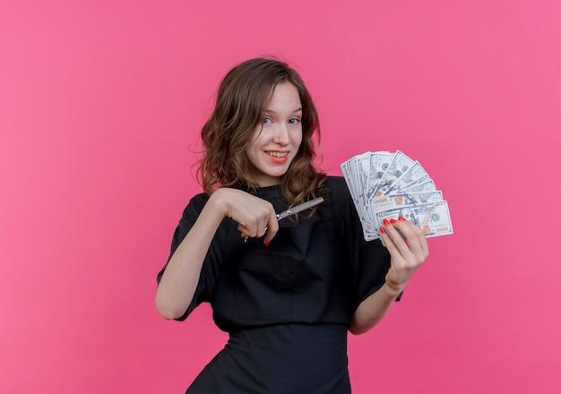Uśmiechnięty młody słowiański fryzjer kobieta ubrana w mundur trzymając pieniądze i nożyczki na białym tle na różowym tle z miejsca na kopię