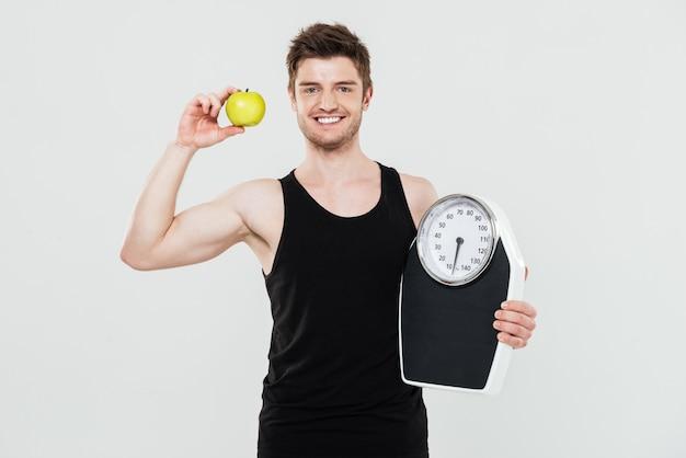 Uśmiechnięty młody sportowa mienie waży i jabłko