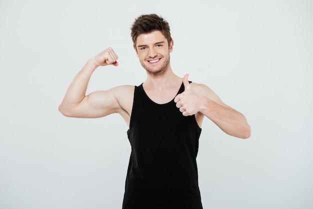 Uśmiechnięty młody sportowiec napina bicepsy i pokazuje aprobata gest