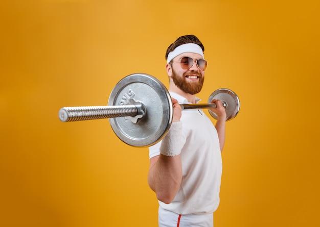 Uśmiechnięty młody sportowiec wykonuje ćwiczenia sportowe ze sztangą