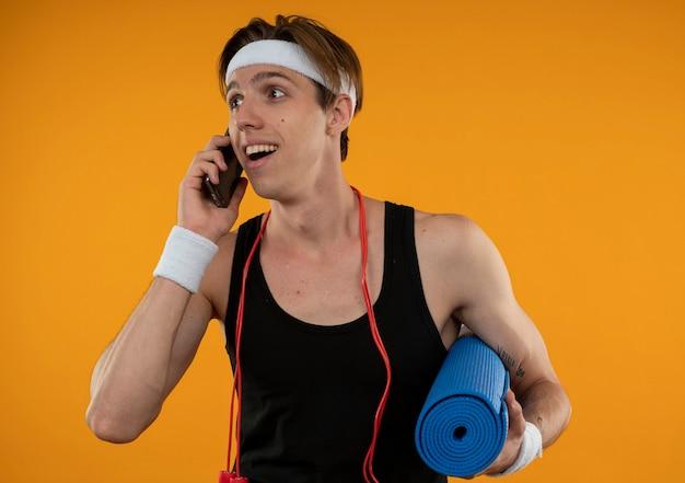Uśmiechnięty młody sportowy facet patrząc na bok z skakanka na ramieniu mówi przez telefon na białym tle na pomarańczowej ścianie