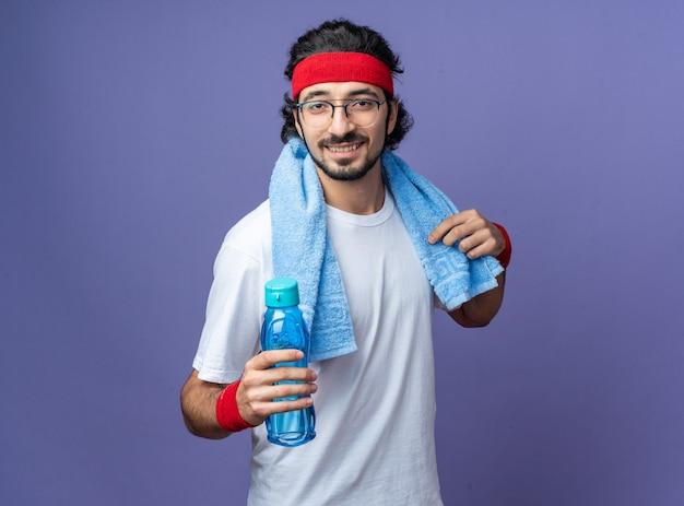 Uśmiechnięty młody sportowy mężczyzna noszący opaskę z opaską na nadgarstek i ręcznik na ramieniu trzymający butelkę z wodą