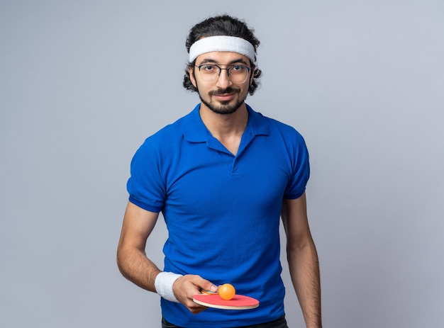 Uśmiechnięty młody sportowy mężczyzna noszący opaskę z opaską na nadgarstek trzymający piłkę do ping ponga na rakiecie