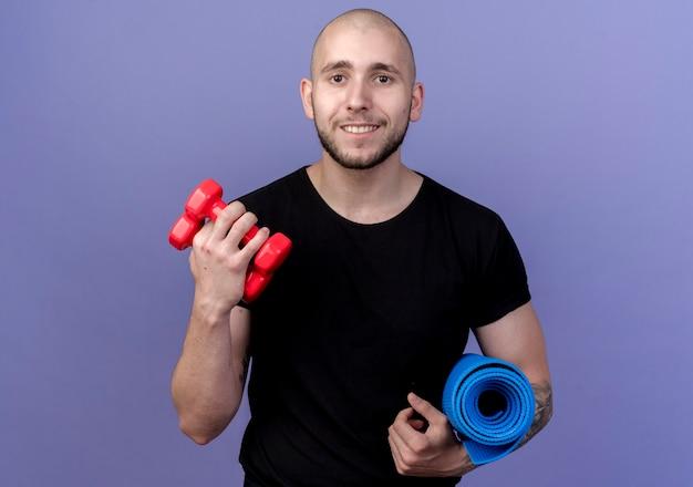 Uśmiechnięty młody sportowy mężczyzna trzyma matę do jogi i hantle na białym tle na fioletowo