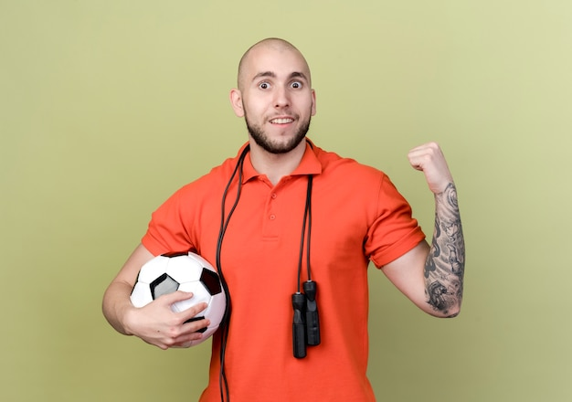 Uśmiechnięty młody sportowy mężczyzna trzyma piłkę z skakanka na ramieniu i pokazuje gest tak na białym tle na oliwkowej ścianie