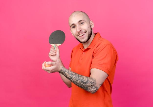 Uśmiechnięty młody sportowy mężczyzna trzyma rakietę do ping-ponga z piłką na białym tle na różowej ścianie