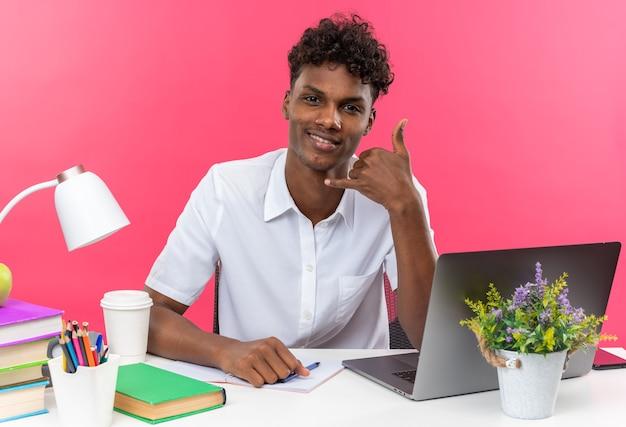 Uśmiechnięty młody student afroamerykański siedzący przy biurku z szkolnymi narzędziami gestykuluje zadzwoń do mnie znak