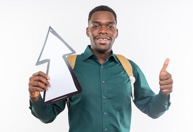 Uśmiechnięty młody student afroamerykański z plecakiem trzymającym strzałkę skierowaną w górę i kciukiem w górę