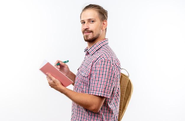 Uśmiechnięty młody student student noszący plecak, piszący coś na notebooku na białym tle na białej ścianie