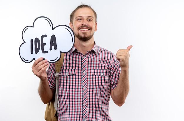 Uśmiechnięty młody student student ubrany w plecak, trzymający bańkę pomysłu pokazujący kciuk na białym tle na białej ścianie