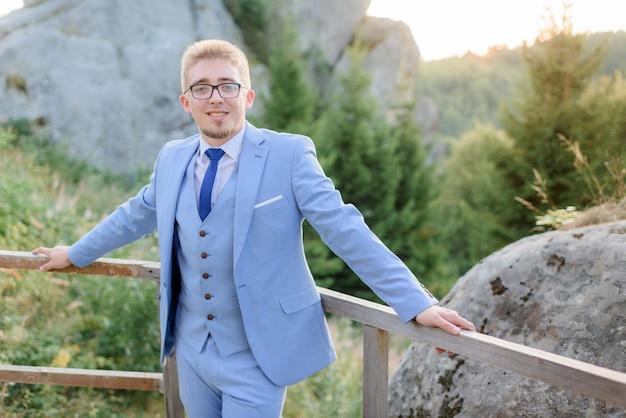 Uśmiechnięty młody stylowy mężczyzna ubrany w niebieski modny garnitur i okulary stoi w pobliżu wielkich skał