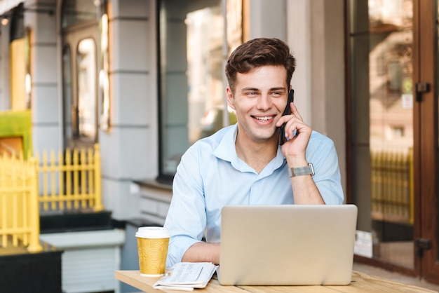 Uśmiechnięty młody stylowy mężczyzna w koszuli rozmawia przez telefon komórkowy