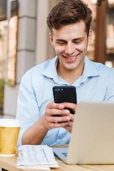 Uśmiechnięty młody stylowy mężczyzna w koszuli za pomocą telefonu komórkowego