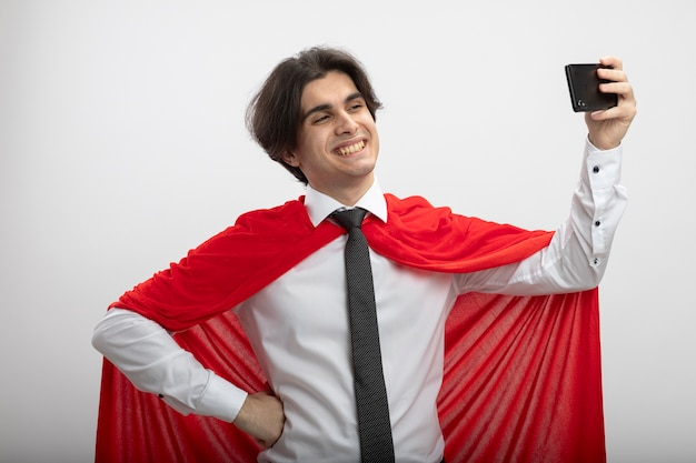 Uśmiechnięty młody superbohater facet ubrany w krawat wziąć aselfie i kładąc rękę na biodrze na białym tle