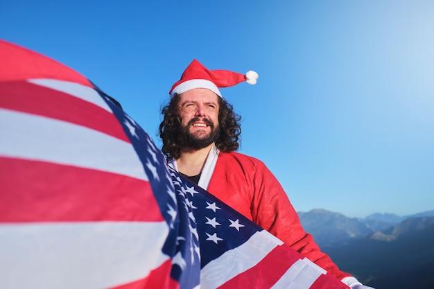 Uśmiechnięty młody święty mikołaj macha amerykańską flagą z górami w tle