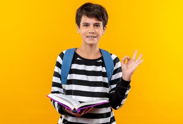 Uśmiechnięty młody szkolny chłopiec noszący plecak trzymający książkę pokazującą dobry gest odizolowany na pomarańczowej ścianie