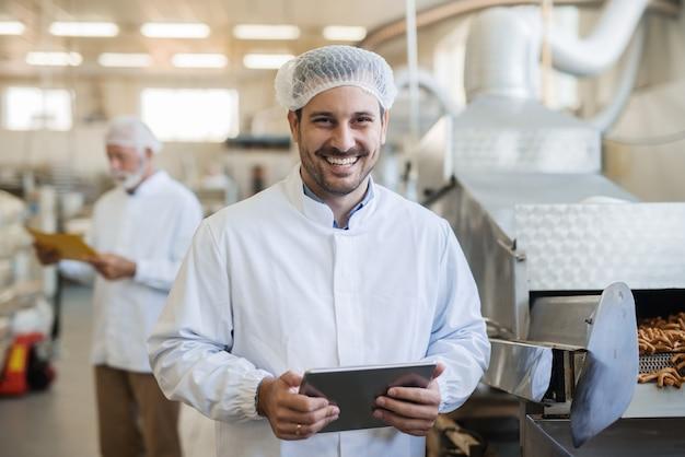 Uśmiechnięty młody technolog za pomocą tabletu. wnętrze fabryki żywności.