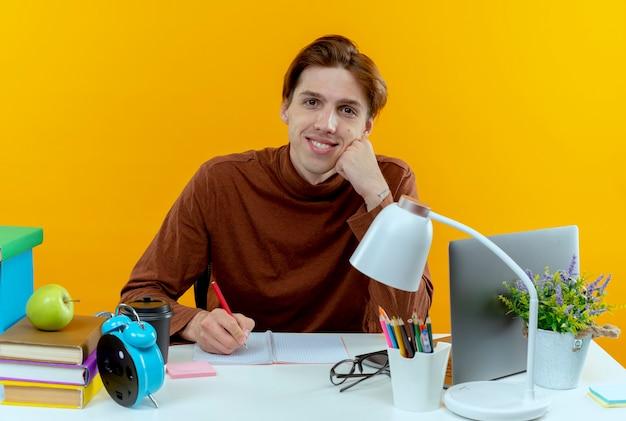 Uśmiechnięty młody uczeń chłopiec siedzi przy biurku z narzędzi szkolnych, pisząc coś na notebooku na żółto