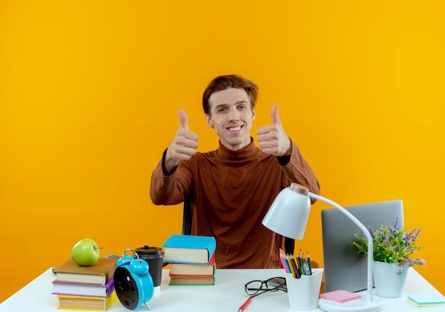 Uśmiechnięty młody uczeń chłopiec siedzi przy biurku z narzędziami szkolnymi kciuki do góry na białym tle na żółtej ścianie