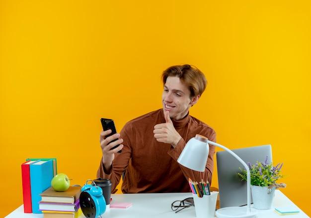 Uśmiechnięty młody uczeń chłopiec siedzi przy biurku z narzędziami szkolnymi, trzymając i patrząc na telefon jego kciuk w górę na białym tle na żółtej ścianie