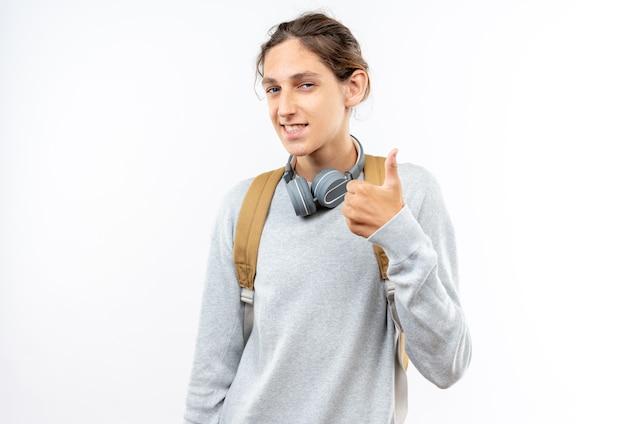 Uśmiechnięty młody uczeń facet nosi plecak ze słuchawkami na szyi pokazując kciuk do góry