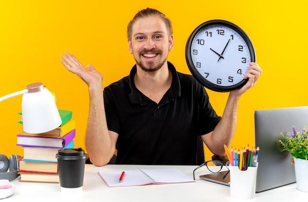 Uśmiechnięty młody uczeń facet siedzący przy stole z szkolnymi narzędziami trzymający zegar ścienny rozkładający rękę