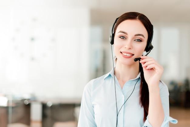Uśmiechnięty młody urzędnik z słuchawki odpowiada w centrum telefonicznym, kobieta opowiada z klientami. portret atrakcyjnego przedstawiciela klienta i pomocy technicznej