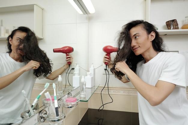 Uśmiechnięty młody wietnamczyk z długimi włosami stojący przed lustrem i używający suszarki do włosów w łazience