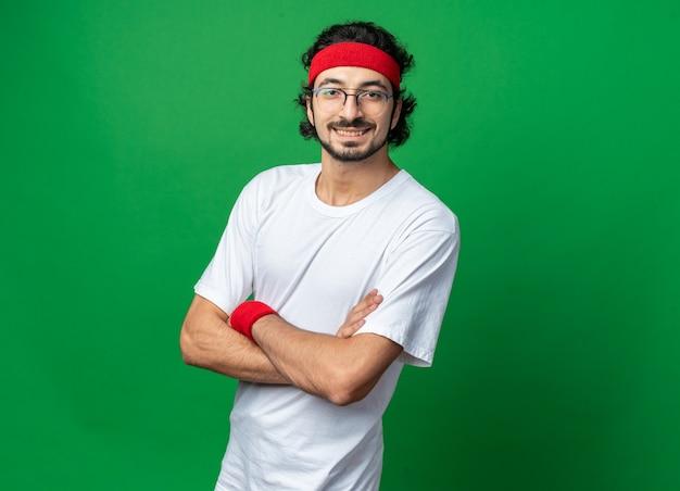 Uśmiechnięty młody wysportowany mężczyzna noszący opaskę z opaską na nadgarstku krzyżującą ręce