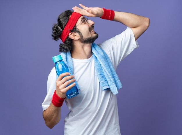 Uśmiechnięty młody wysportowany mężczyzna noszący opaskę z opaską na rękę i ręcznikiem na ramieniu, trzymający butelkę z wodą kładącą rękę na czole