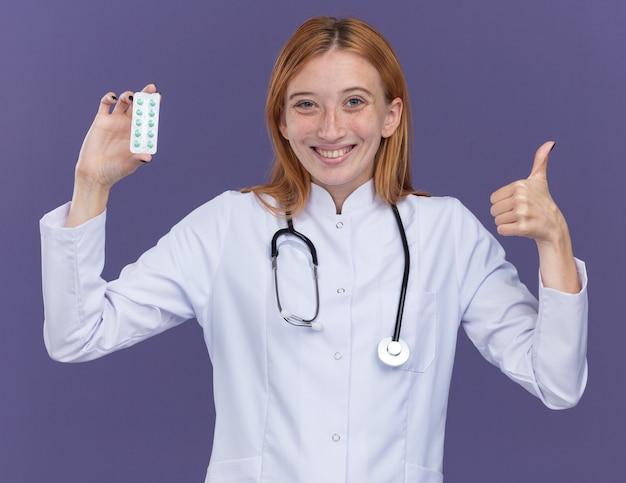 Uśmiechnięty młody żeński imbirowy lekarz ubrany w szatę medyczną i stetoskop pokazujący paczkę tabletek medycznych do kamery pokazujący kciuk odizolowany na fioletowej ścianie