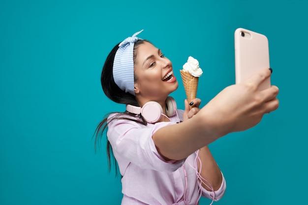 Uśmiechnięty model bierze selfie, trzyma lody.