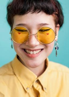 Uśmiechnięty model jest ubranym żółtych szkła