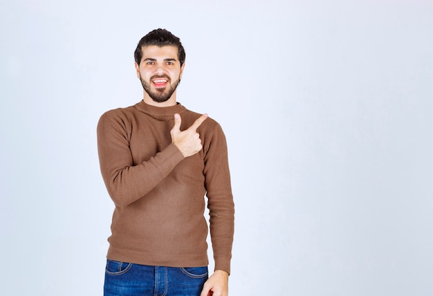 Uśmiechnięty model młodego człowieka stojącego i wskazującego palcem wskazującym. zdjęcie wysokiej jakości