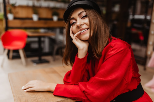 Uśmiechnięty model o ładnej buzi atrakcyjnie wygląda w obiektywie. portret europejskiej dziewczyny w stylu paryskim z krótkimi brązowymi włosami