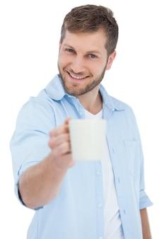 Uśmiechnięty model oferuje kubek
