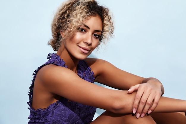 Uśmiechnięty model w modne letnie ubrania siedzi w pobliżu niebieską ścianą