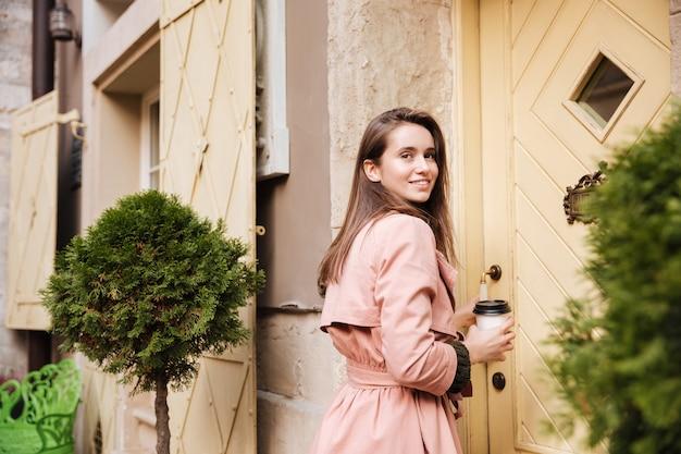 Uśmiechnięty model w płaszczu z kawą. s