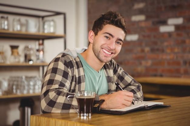 Uśmiechnięty modniś ma kawę i pisze w planiście