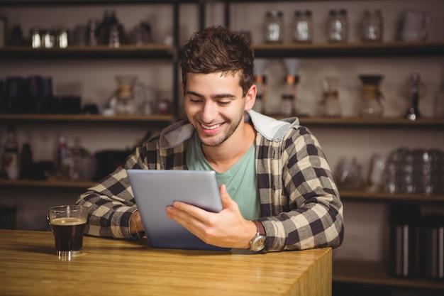 Uśmiechnięty modniś ma kawę i używa pastylka komputer