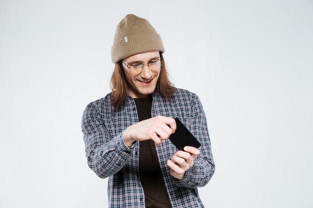 Uśmiechnięty modniś w eyeglasses bawić się na smartphone
