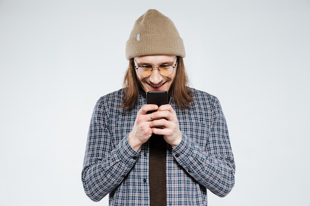 Uśmiechnięty modniś w eyeglasses używać smartphone