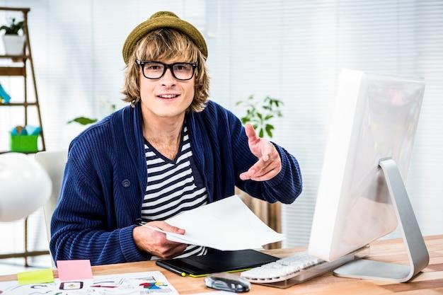 Uśmiechnięty modnisia biznesmen pracuje przy jego biurkiem