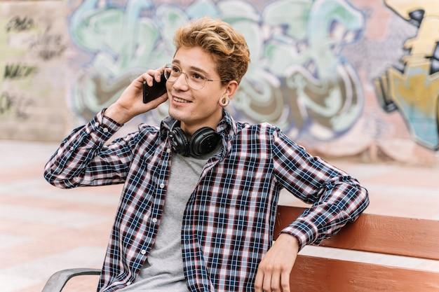 Uśmiechnięty modnisia mężczyzna patrzeje stronę podczas gdy opowiadający przyjaciel na smartphone