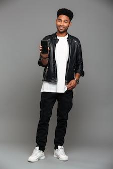 Uśmiechnięty modny afrykański facet stojący z ręką w kieszeni, pokazując pusty ekran telefonu komórkowego, patrząc