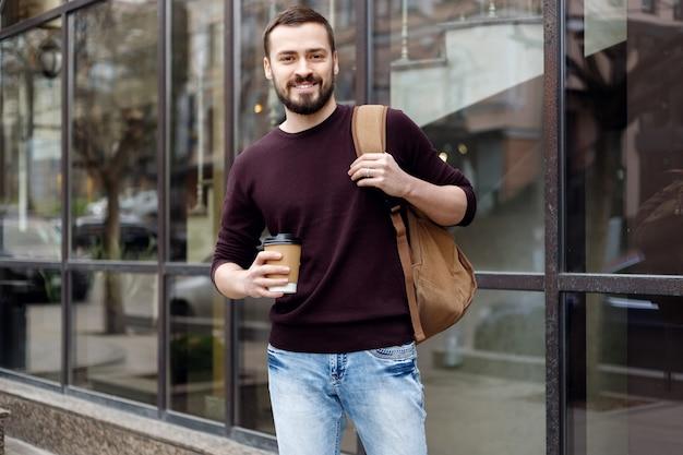 Uśmiechnięty modny facet w kapeluszu, spacerujący po mieście z filiżanką kawy w ręku. obraz uśmiechniętego mężczyzny w wieku 30 lat w okularach spacerującego ulicą miasta i trzymającego kawę na wynos